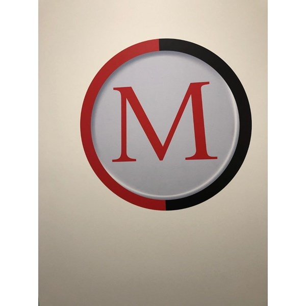 One of ManTechs logos as a wall graphic, to tie in all of the black and red themed signage and walls in the building.