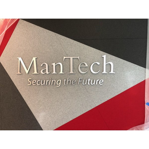 Some elegant, brushed silver, dimensional lettering for ManTech. Their logo and tagline installed on wall.